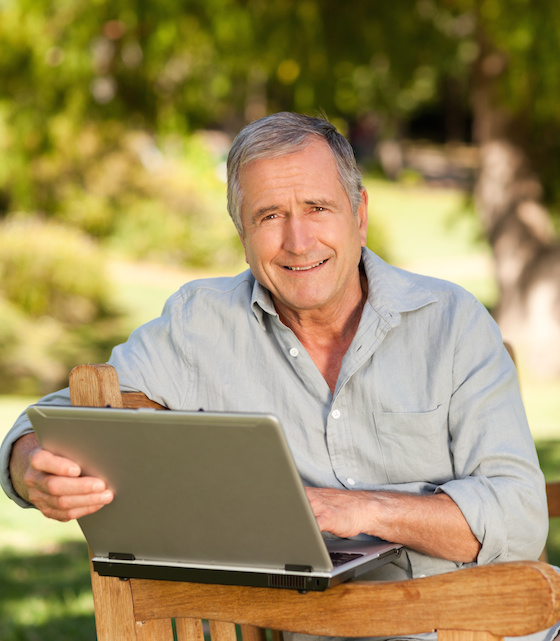 Retired man working on his laptop in the park