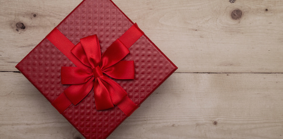 Closeup of red gift box with ribbon on vintage wooden background